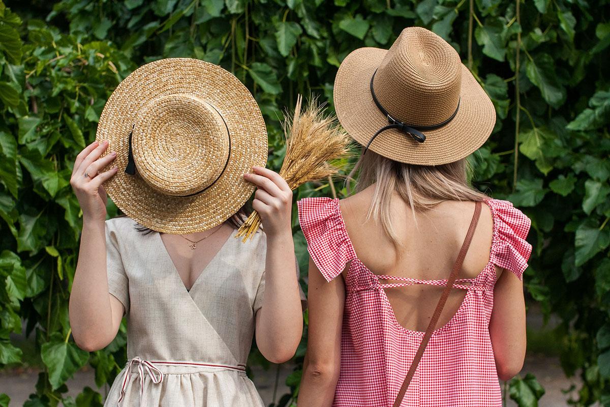 Two girls wear trendy straw hats