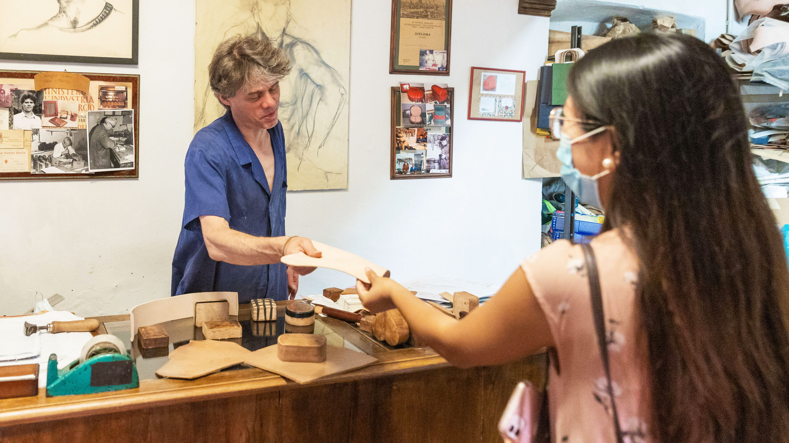 An artisan shows to a girl his leather during an artisan tour in Florence