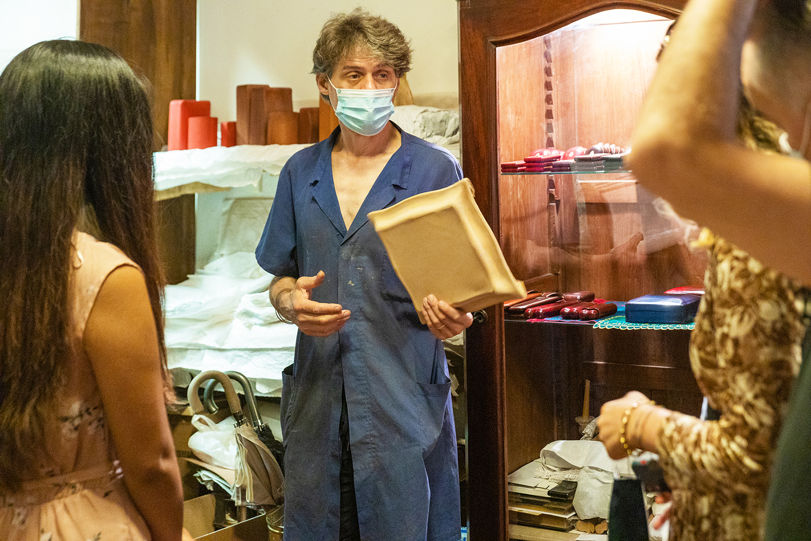 Leather craftsman Simone Taddei explains his work to a group in Florence