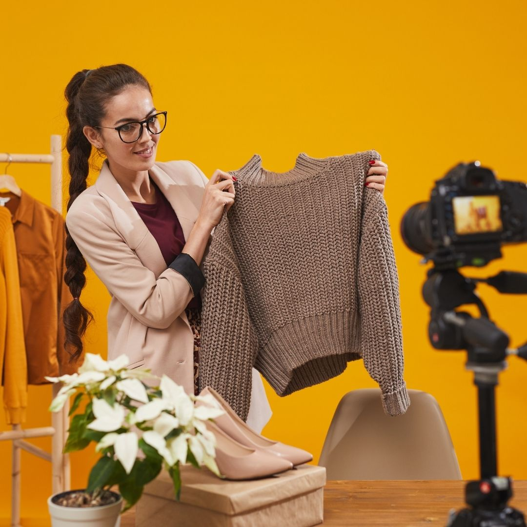 A teacher shows a sweater during an online fashion class