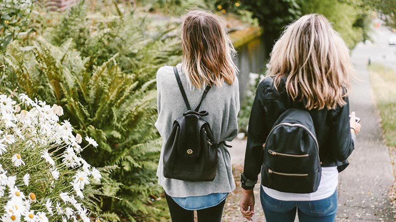 Two women walk with their black backpacks