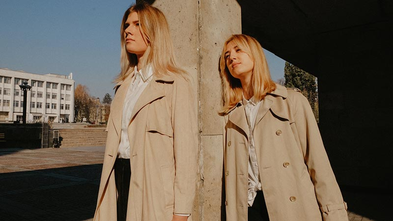 Two girls with their beige trench coats
