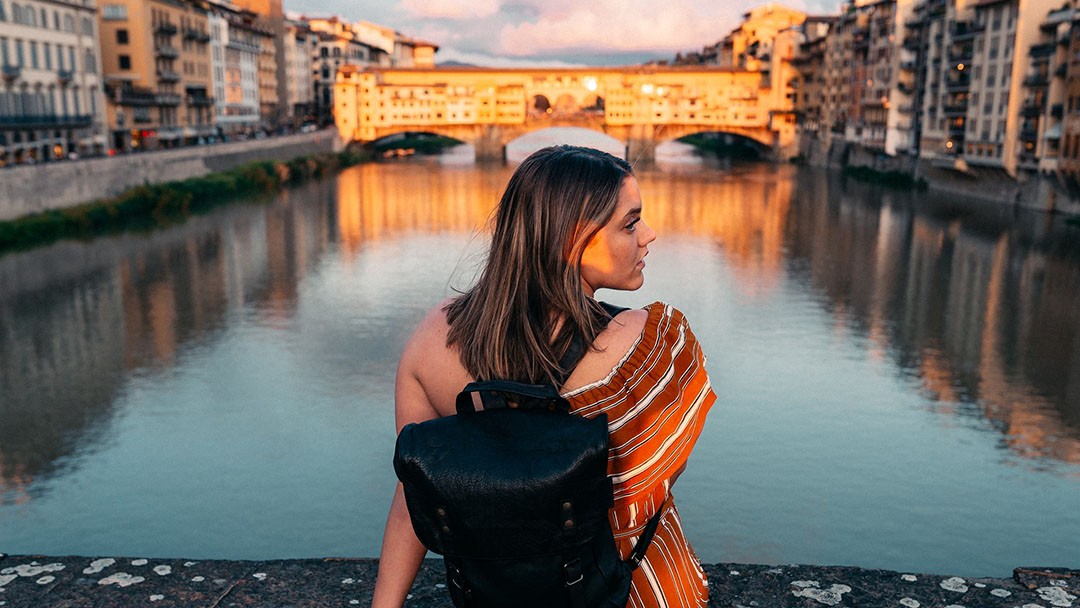 A young woman with a backpack enjoys sunsets in Florence